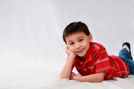 studio shot of cute asian boy laying on stomach