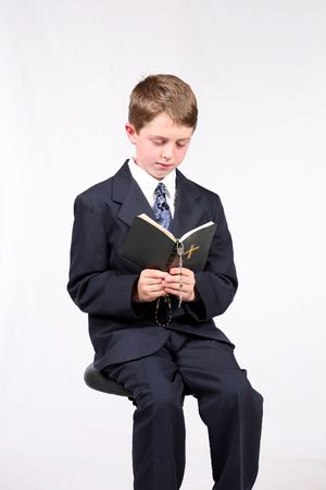 young boy seated reading a bible and holding a rosary photo