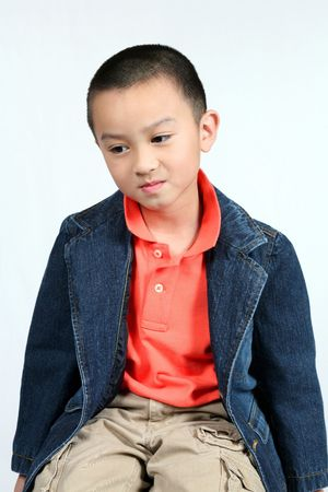 cute asian boy seated isolated on white background