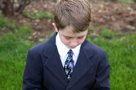 closeup of young boy in suit looking down Stock Photo