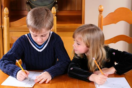 pretty young girl looking at boys homework Stock Photo