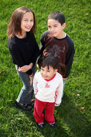 3 multi-racial kids outside in grass