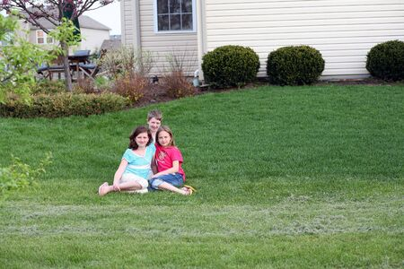 children sitting in yard outside house Stock Photo - 3054946