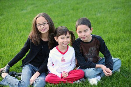 3 multi-racial kids sitting in grass