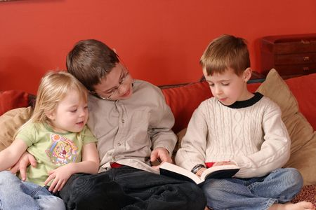 storytime: interior shot of 3 children reading a book Stock Photo