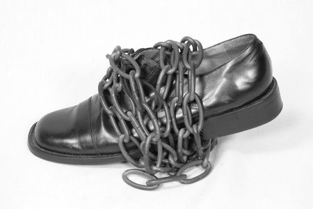 chainlinks: black oxford dress shoe wrapped in bronze chain Stock Photo