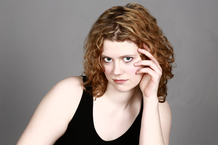 beautiful girl with curly hair flirting with camera and hand by face