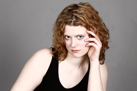 Belle fille aux cheveux bouclés flirter avec une caméra et la main par le visage Banque d'images - 81588169