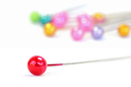 collocation: Photos of push pins focuses on the foreground red push pins on a white background