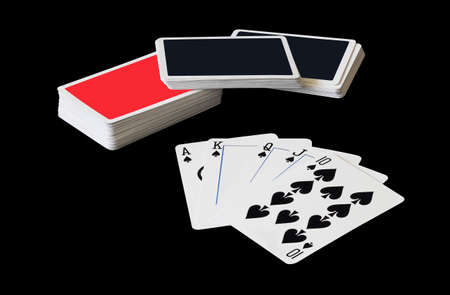royal flush: Stacks of playing cards and Royal Flush of spade in poker game isolated on black background Stock Photo