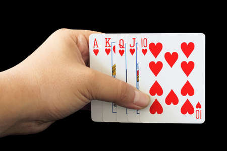 royal flush: Royal Flush of heart in poker game in the hand on a black background