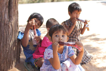 unidentified: Unidentified children are enjoying eating ice cream at wayside : on Feb 02, 2014 Bagan in Myanmar
