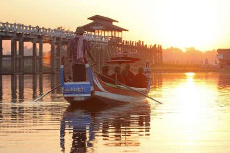 boatman: Buddhist monks sit in a boat  at U Bein bridge, Mandalay in Myanmar on Feb 03, 2014 : U Bein bridge is famed for the longest teak bridge in the world.