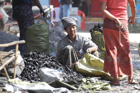 smut: Women selling wood charcoal placed on the ground among the hot sunlight at Mandalay in Myanmar on Feb 03, 2014