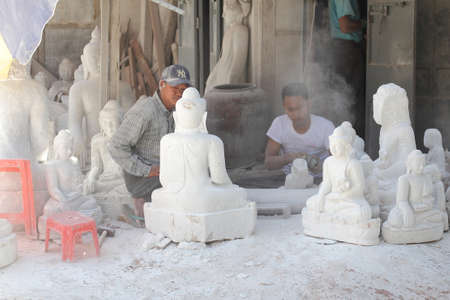 carving tool: Burmese man use tool carving a marble Buddha statue, outdoors at Mandalay in Myanmar on Feb 03, 2014 : The Buddha statue made for sale and brought to the Myanmar temple Editorial