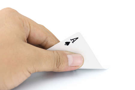 focuses: Closeup photos that focuses on the ace card of spades in the hand on white background Stock Photo