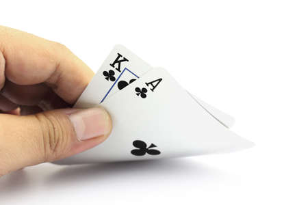 jack of clubs: Closeup photos that focuses on the black jack with King card and ace card of clubs in the hand on white background Stock Photo