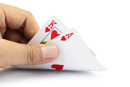 black jack: Closeup photos that focuses on the black jack with King card and ace card of heart in the hand on white background