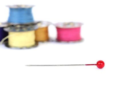 collocation: Red push pins and background of sewing thread on a white background, Focuses on the red push pins Stock Photo