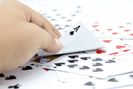 focuses: Closeup photos that focuses on the ace card of spade in the hand,on the background from the stack of cards.