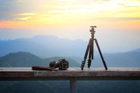 Dslr photo camera and tripod is travel photographer equipment placed on a wooden terrace with a beautiful background of sunrise.Traveling and Relax Concept