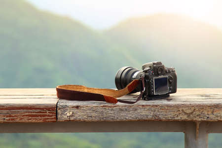 Dslr photo camera is travel photographer equipment placed on a wooden terrace with a beautiful background of natural.Traveling and Relax Concept