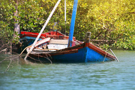 boat accident: Wreck fishing boat floating in the water in the mangrove forest at Thailand Stock Photo