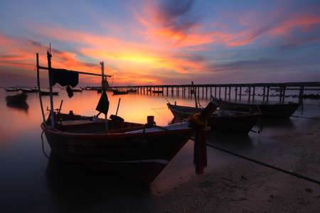 beached: Silhouette natural background of small fishing boats moored beached on the beach during time the sunset and the beautiful natural of the colorful sky at Bang Phra beach , Chonburi province in Thailand Stock Photo