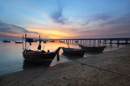 beached: Small fishing boats moored beached on the beach during time the sunset and the beautiful natural of the colorful sky at Bang Phra beach , Chonburi province in Thailand