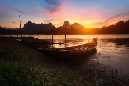 Silhouette of passenger ships moored beached during time the sunset at beautiful natural attractions in Ratchaprapha Dam at Khao Sok National Park, Surat Thani Province in Thailand. 免版税图像