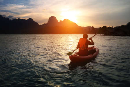 Silhouette scenery during sunset with a man paddling the kayak at natural attractions in Ratchaprapha Dam,Khao Sok National Park,SuratThani Province in Thailand. Traveling and recreation Concept.