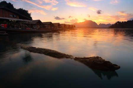 Silhouette scenery during sunrise of houseboat resort at lake river in natural attractions,Ratchaprapha Dam at Khao Sok National Park,Surat Thani Province in Thailand.Traveling , recreation Concept