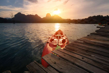 Silhouette scenery during sunset with kayak,canoe at natural attractions in Ratchaprapha Dam,Khao Sok National Park,SuratThani Province in Thailand. Traveling and recreation Concept.