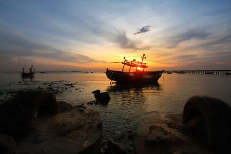 Silhouette natural background of small fishing boats moored beached on the beach during time the sunset and the beautiful natural of the colorful sky at BangPhra beach , Chonburi province in Thailand Stock Photo