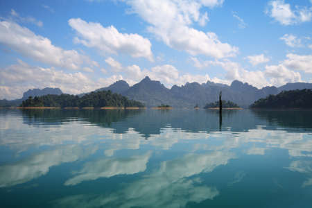 Beautiful scenery of the beautiful water reflection with clear sky at lake river in natural attractions,Ratchaprapha Dam at Khao Sok National Park,Surat Thani Province in Thailand.