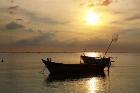 beached: Silhouette natural background of small fishing boats moored beached on the beach during time the sunset and the beautiful natural of the colorful sky at BangPhra beach , Chonburi province in Thailand Stock Photo