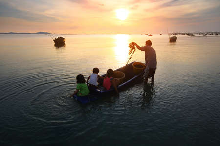 livelihoods: Silhouette scenery of the livelihoods of fishermen during time the sunset and the beautiful natural of the colorful sky at Bang Phra beach , Chonburi province in Thailand.