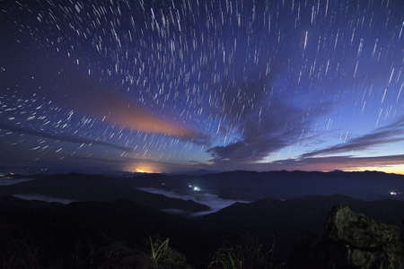 Beautiful scenery of the startrail on sky at night at Doi Pha Phung at Nan province in Thailand. Long exposure shooting and high iso used make this photo have noise Stock Photo