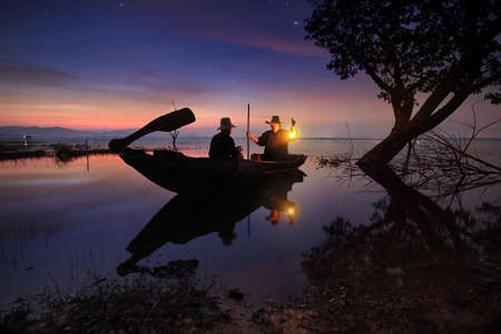 livelihoods: Beautiful scenery of nature and livelihoods of fishermen who are prepare boating fishing in morning time before sunrise at Bang Pra Reservoir , Chonburi province in Thailand Stock Photo