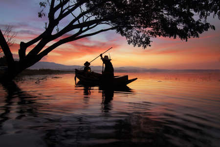 livelihoods: Silhouette of fishermen using harpoon to catch fish at the Bangpra lake with beautiful scenery of nature during sunrise time. Bang Pra Reservoir at Chonburi province in Thailand Stock Photo
