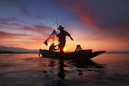 Silhouette of fishermen using nets to catch fish at the Bangpra lake with beautiful scenery of nature during sunrise time. Bang Pra Reservoir at Chonburi province in Thailand