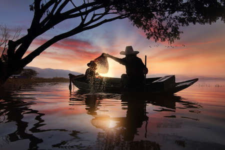 livelihoods: Silhouette of fishermen using coop-like trap catch fish at the Bangpra lake with beautiful scenery of nature during sunrise time. Bang Pra Reservoir at Chonburi province in Thailand Stock Photo