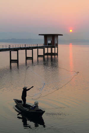 catchment: Silhouette of fishermen using nets to catch fish at the Bangpra lake with beautiful scenery of nature during sunrise time. Bang Pra Reservoir at Chonburi province in Thailand