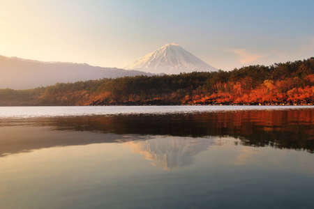 Beautiful scenery during sunrise of Lake Saiko in Japan with beautiful water reflection of Mountain Fuji. Travel and Attraction Concept