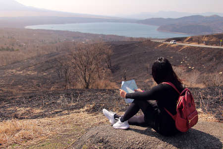Traveler woman sitting at the mountain surrounded by beautiful natural to studying the route from maps in hand to find attractions in Japan. Travel and active lifestyle concept Stock Photo