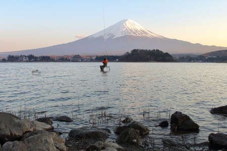Fisherman in the lake kawaguchiko and Mountain Fuji in Japan. This is a very popular for photographers and tourists. Travel and natural Concept