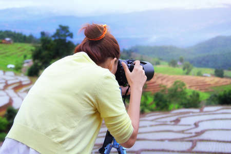 Woman photographer she is photographing the beautiful natural of the rice terraces in the morning. Travel and natural concept.
