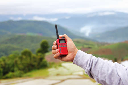 Radio communication(walkie-talkie radio) in hand, on Natural background Stock Photo