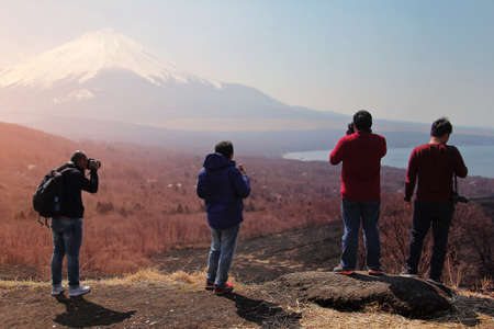 Group of traveler who love photography are standing admire the beautiful nature of Mt. Fuji in Japan. Travel and Attractions Concept. Stock Photo
