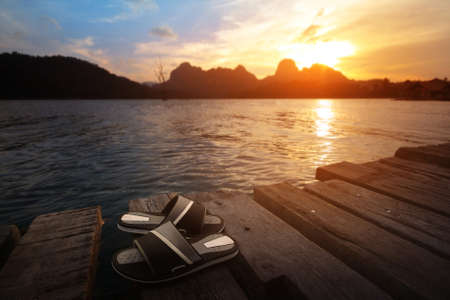 flip flops: Sandals on the old wooden dock and scenery during sunset of lake river at natural background. Traveling and recreation Concept